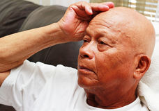 Drowsy. An elderly balding Asian or Filipino man holding his head feeling drowsy stock photography