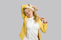 Drowsy business woman stretching, grey background. Attractive tired fatigued young manager stretching extending arms, back, shoulders with closed eyes isolated royalty free stock images
