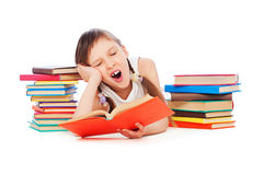 Drowsy little girl with books. Portrait of drowsy little girl with books royalty free stock image
