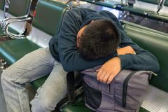 Drowsy man drooping head on backpack to sleep Royalty Free Stock Photo