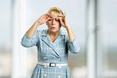Drowsy mature woman in dress. Sleepy tired white-skin woman rubbing her eyes by hands on blurred background royalty free stock photo