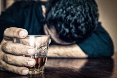 Drrunk man holding a drink and sleeping on a table Royalty Free Stock Photos