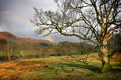 Lake District country scene. Rainbow above pike at Elterwater Royalty Free Stock Image