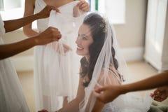 Drużka pomaga panny młodej w być ubranym przesłonę Obrazy Royalty Free