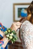 Drużka pomaga panny młodej z ślubną suknią zdjęcie stock