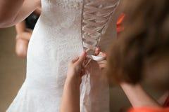 Drużka ubiera panny młodej dla dnia ślubu Drużka pomaga z białą suknią przed ceremonią Luksus bridal zdjęcia royalty free
