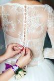 Drużki pomaga wiązać jej ślubną suknię Ranek panna młoda obrazy royalty free