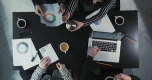 Drużyna dyskutuje biznesowych problemy i pije herbaty przy depresją - prędkość Użycie grafika, rozkłady i zbiory