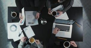 Drużyna dyskutuje biznesowych problemy i pije herbaty przy pełną prędkością Użycie grafika, rozkłady i zbiory