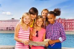 Drużyna dzieci stoi wpólnie z mapą Zdjęcia Royalty Free