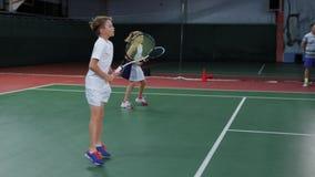 Drużyna dziewczyna i chłopiec bawić się tenisa na salowym sądzie Młody graczów ćwiczyć zbiory