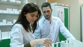 Drużyna farmaceuty patrzeje medycynę i opowiada przy szpitalną apteką Zdjęcia Royalty Free