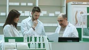 Drużyna farmaceuty pracuje przy apteki apteką, starsza farmaceuta no satysfakcjonuje z uczniami akcydensowymi Zdjęcie Stock