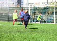 Drużyna futbolowa - chłopiec w czerwonym i błękitnym, zieleni sztuki jednolita piłka nożna na zielenieją pole Gra zespołowa, szko obraz royalty free