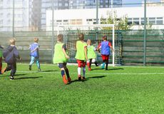Drużyna futbolowa - chłopiec w czerwonym i błękitnym, zieleni sztuki jednolita piłka nożna na zielenieją pole Gra zespołowa, szko zdjęcie royalty free