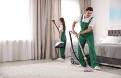 Drużyna janitors czyści sypialnię z wyposażeniem obrazy stock