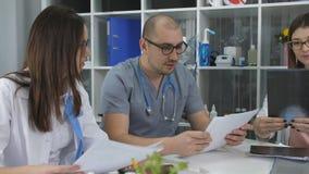 Drużyna lekarki ma spotkania w biurze Trzy lekarki przy biurkiem w biurze doradca zbiory wideo