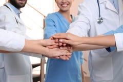 Drużyna lekarzi medycyni stawia ręki wpólnie indoors t?a b??kitny poj?cia ludzie sylwetek nieba jedno?ci fotografia royalty free