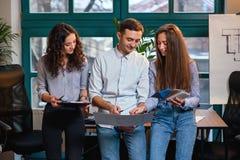 Drużyna młody caucasian inżynier stoi blisko stołu podczas gdy opowiadający nowego pomysł o budować plany w eleganckim zdjęcie stock