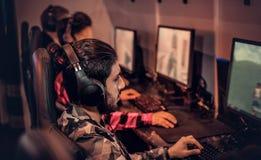 Drużyna nastoletni gamers bawić się w dla wielu graczy gra wideo na komputerze osobistym w hazardu klubie zdjęcie royalty free