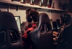 Drużyna nastoletni gamers bawić się w dla wielu graczy gra wideo na komputerze osobistym w hazardu klubie zdjęcie stock