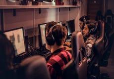 Drużyna nastoletni gamers bawić się w dla wielu graczy gra wideo na komputerze osobistym w hazardu klubie fotografia royalty free