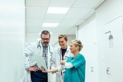 Drużyna studenci medycyny patrzeje raport medycznego w szpitalnym korytarzu zdjęcia royalty free