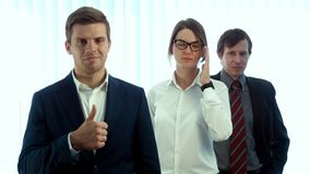 Drużyna trzy pomyślnego ludzie biznesu patrzeje w kamerę pokazuje wielkiego dużego palec up zdjęcie wideo
