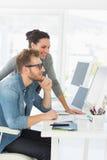 Drużyna uśmiechnięci projektanci patrzeje komputer Obrazy Stock