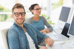 Drużyna uśmiechnięci projektanci z mężczyzna patrzeje kamerę Obraz Stock