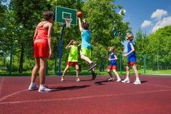 Drużyna w kolorowych mundurach bawić się mecz koszykówki Zdjęcia Royalty Free