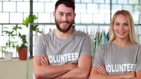 Drużyna wolontariuszi ono uśmiecha się przy kamerą daje aprobatom zbiory