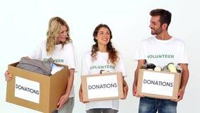 Drużyna wolontariuszi ono uśmiecha się przy kamery mienia darowiznami boksuje zdjęcie wideo