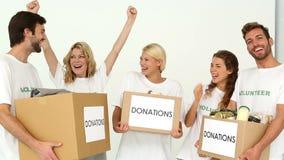 Drużyna wolontariuszi trzyma darowizny rozweselać i pudełka zbiory