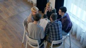 Drużynowa komunikacja, grupa pięć ludzi dyskutuje coś z uśmiechem podczas gdy siedzący przy biuro stołem obrazy stock