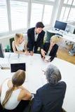 Drużynowy opowiadać w biznesowym spotkaniu przy konferencyjnym stołem Zdjęcia Stock
