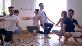 Drużynowy poparcie, szczęśliwi młodzi ludzie kucnięć, wpólnie i wtedy oklaskujący each inny na grupowej terapii zdjęcie wideo