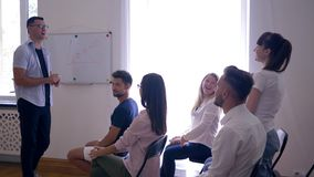 Drużynowy szkolenie, mówca przedstawia nowego plan biznesowego na whiteboard i szczęśliwa młoda dziewczyna pyta pytania na konwer zbiory wideo