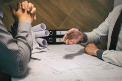 Drużyna budowy inżynieria lub architekta partner dyskutujemy projekt podczas gdy sprawdzać informację na rysować i kreślić obraz stock