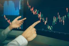 Dru?yna faktorscy handlarscy ludzie biznesu wskazuje wykresu i analizy rynek papier?w warto?ciowych na ekranie komputerowym w biu obrazy royalty free