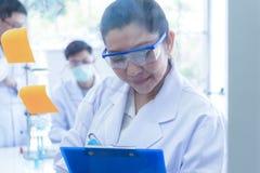 Dru?ynowi praca naukowowie analizuje nauka dane i ocenia mikroskopu sukces dla warsztata obrazy stock
