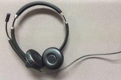 Druciana słuchawki przy kątem na Szarym Tekstylnym tle Fotografia Stock