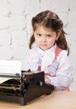 Drucke des kleinen Mädchens auf der alten Schreibmaschine Lizenzfreie Stockbilder