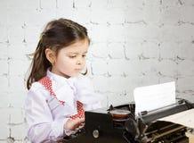 Drucke des kleinen Mädchens auf der alten Schreibmaschine Stockbild
