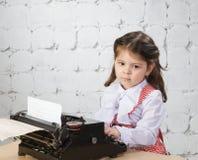Drucke des kleinen Mädchens auf der alten Schreibmaschine Stockbilder
