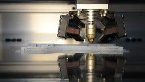 Drucker 3d, der graue Gegenstände auf Spiegelreflektierender Oberflächennahaufnahme druckt
