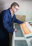 Drucker, der eine Auflagenstärke überprüft Stockfoto