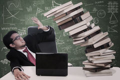 Druckgeschäftsmann mit fallenden Büchern an der Klasse Stockfotografie