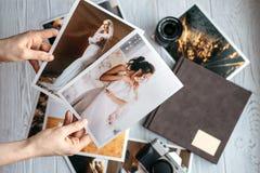 Druckheiratsfotos mit der Braut und dem Bräutigam, eine Weinleseschwarzkamera, photoalbum und Frauenhände mit zwei Fotos lizenzfreie stockfotografie