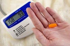 Druckmessgerät und Tablette in der Hand Apparat stockfotos